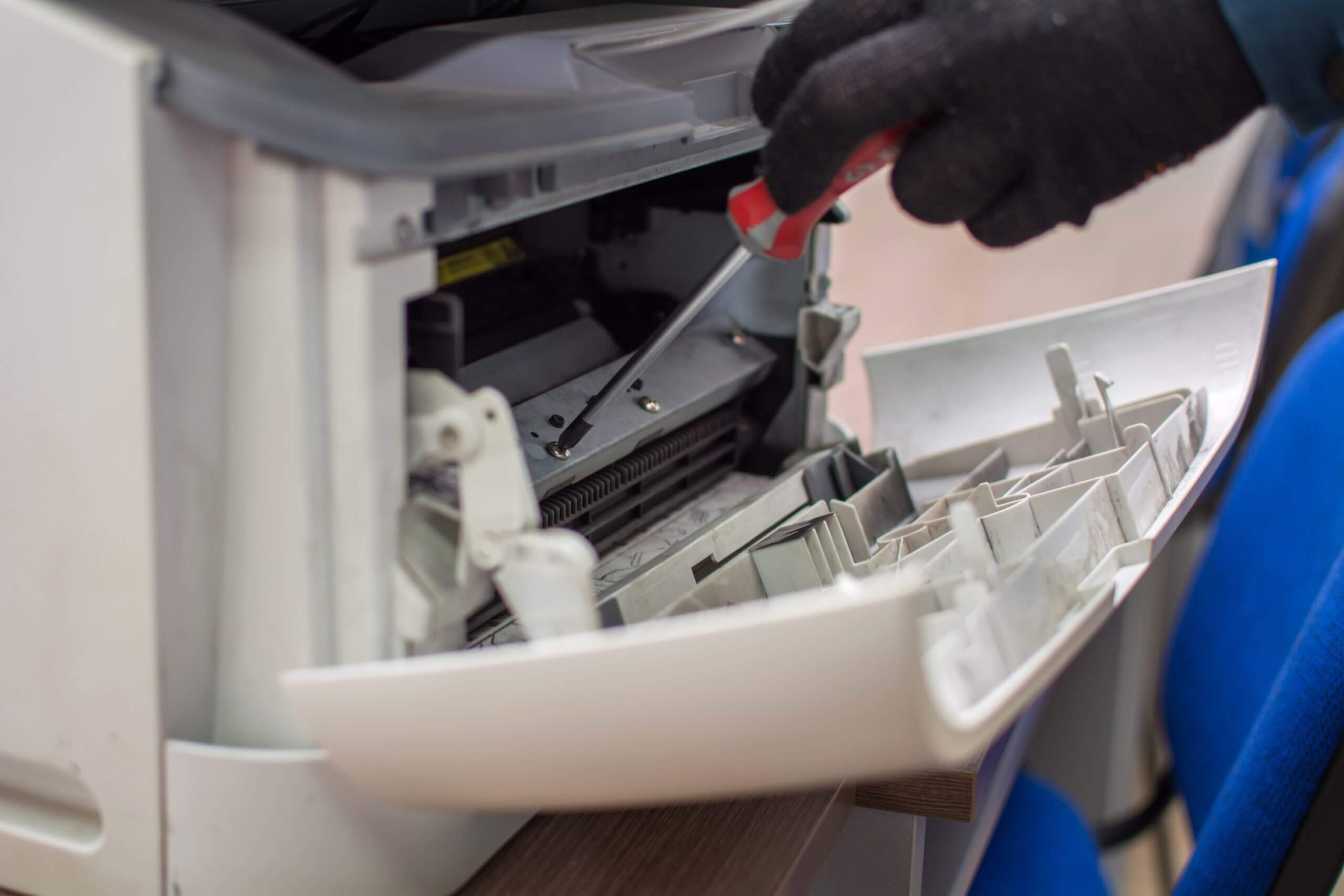 The specialist repairman serves or repairs the laser printer with a screwdriver and a brush. Servicing of copiers and printers